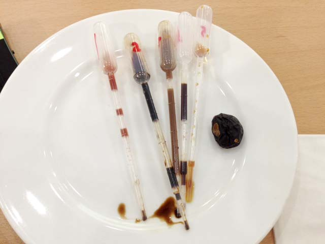 "Nordic Food Lab tasters: apple balsamic vinegar, elderflower vinegar, grasshopper garum, pheasant garum, malt ""black bean"" sauce, and dried plum"