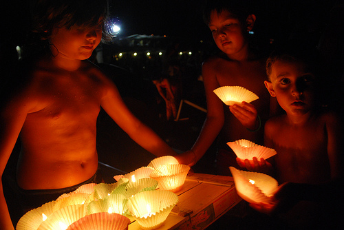 Boys preparing lights to float out to sea during festival time by Kekkoz