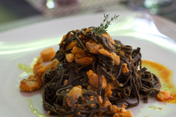Squid ink pasta with fish ragout and spicy sausage