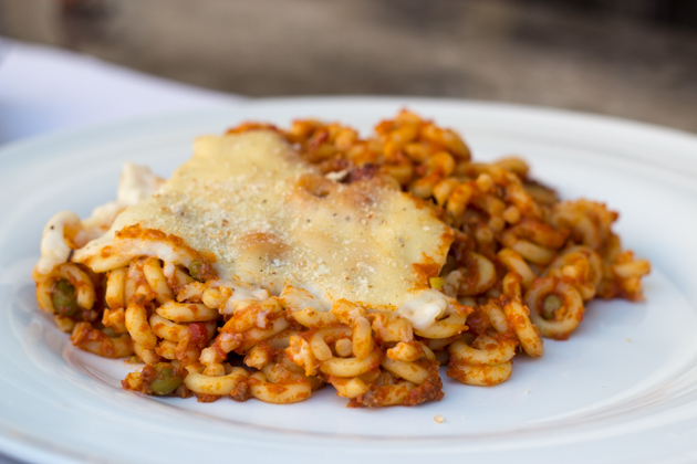 Anelletti pasta baked with meat sauce, peas and cheese