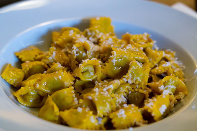Agnolotti (stuffed pasta filled with mixed meats which can be roasted, braised, or stewed, bound with eggs, and mixed with a vegetable such as escarole, chard, cabbage, spinach, or rice, boiled in water or broth, served with sugo di arrosto (roast meat gravy); butter, sage, and Parmigiano-Reggiano cheese; or plain)