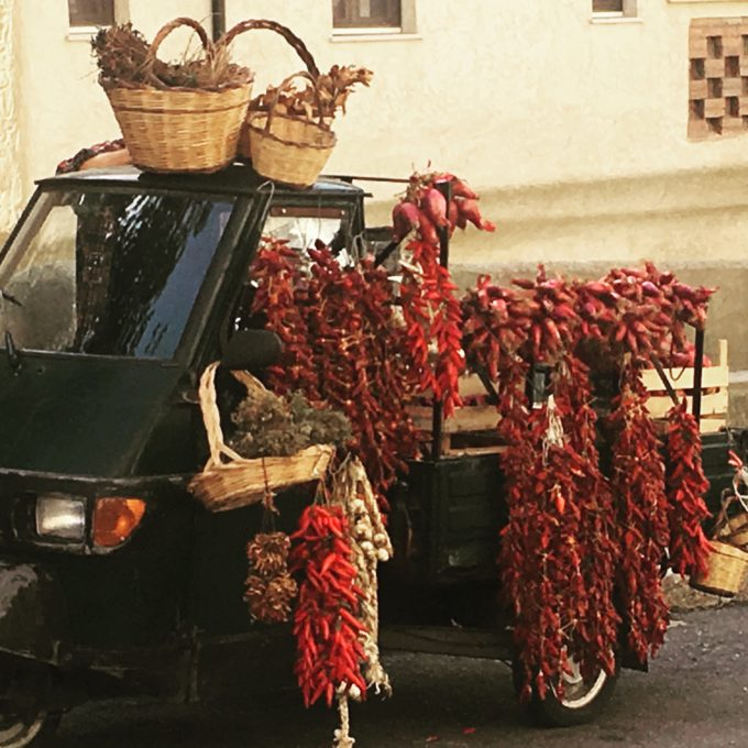 A tre ape cart selling local Calabrian products: chillies, oregano and Tropea onions
