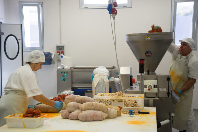 The ground fat is mixed with the meat and chilli mixture (back right), it is then fed into a machine which expresses it into a casing (right hand side) and then hand tied, pricked and hung (front left).